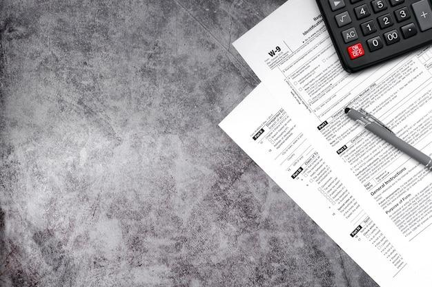 Belastingvermindering en belastingformulieren met een handtekeningpen en een rekenmachine om belastingen op een grijs vlak te berekenen
