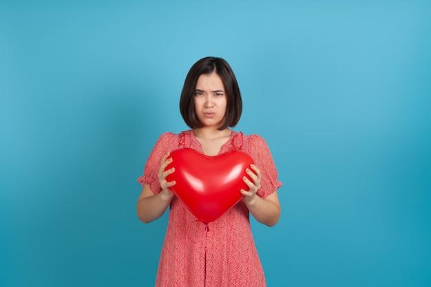 Beledigd door een slecht geschenk, houdt een jonge aziatische vrouw een rode hartvormige ballon in haar handen