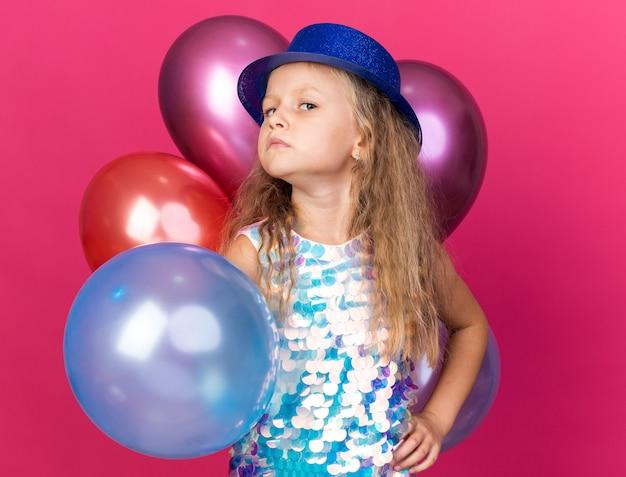 Beledigd klein blond meisje met blauwe feestmuts staande met heliumballonnen geïsoleerd op roze muur met kopieerruimte