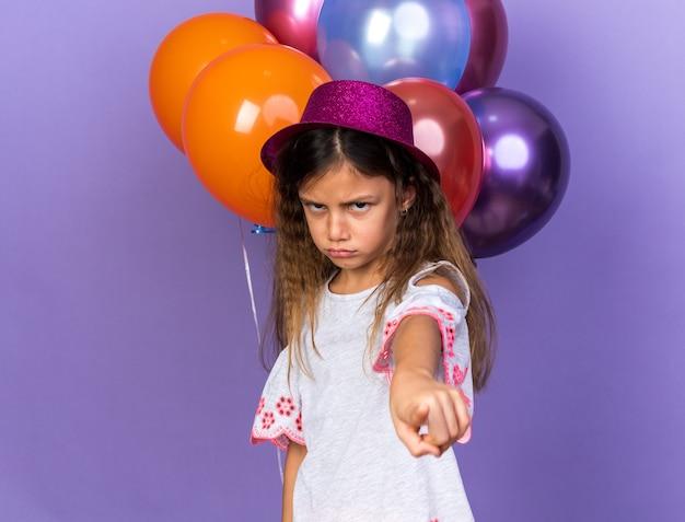Beledigd klein kaukasisch meisje met violet feestmuts wijzend voor heliumballonnen geïsoleerd op paarse muur met kopieerruimte