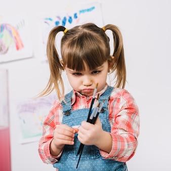 Beledigd meisje dat zich met verfborstels in handen bevindt