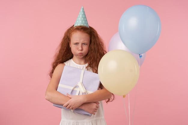 Beledigd meisje met lang foxy haar met ingepakte huidige doos, droevig kijkend en pruilend, geïsoleerd op roze met gekleurde luchtballonnen, gekleed in witte elegante jurk