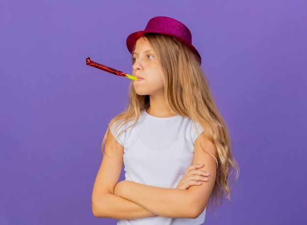 Beledigd mooi meisje in vakantie hoed blaast fluitje, verjaardagsfeestje concept permanent over paarse achtergrond