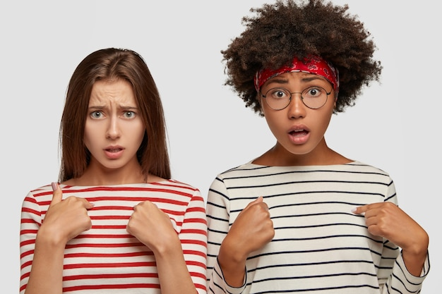Beledigd verontwaardigd geschokt gemengd ras vrouwen wijzen naar zichzelf, worden boos door iemand, wachten op uitleg, hebben vraagtekens geplaatst, wachten op de mening van vrienden, voelen zich bezorgd en onzeker