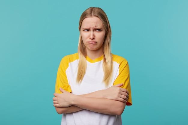 Beledigde jonge aantrekkelijke blonde dame die haar handen op de borst kruist en droevig haar gezicht grimast terwijl ze opzij kijkt, gekleed in vrijetijdskleding terwijl ze poseren op blauwe achtergrond