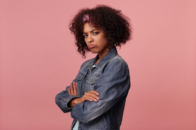 Beledigde jonge donkere krullende brunette vrouw met kort kapsel dragen kleurrijke hoofdband en haar lippen draaien tijdens het kijken, gekleed in vrijetijdskleding