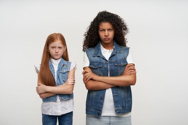 Beledigde jonge donkerhuidige brunette dame en roodharig mooi klein meisje kijkt droevig met gevouwen lippen en kruising handen op de borst, geïsoleerd op wit