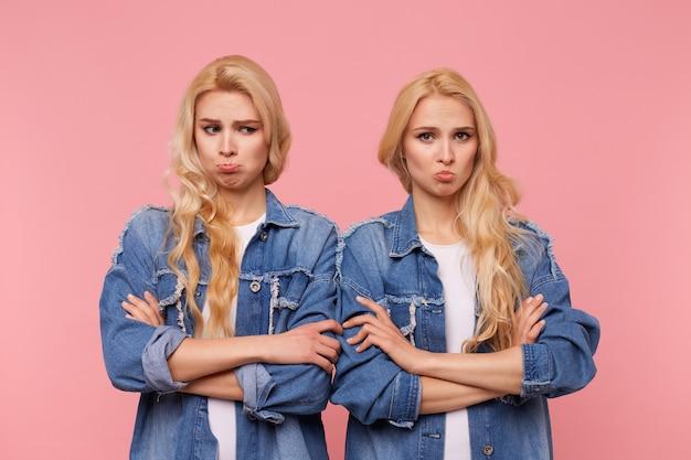 Beledigde jonge mooie blonde dames met krullen die handen op de borst vouwen terwijl ze helaas lippen pruilen, gekleed in vrijetijdskleding terwijl ze poseren op roze achtergrond