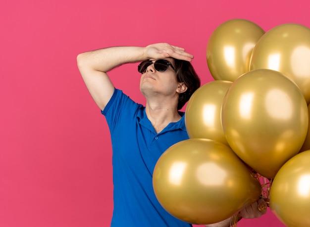 Beledigde knappe blanke man in zonnebril houdt heliumballonnen vast en legt hand op voorhoofd