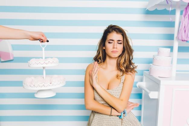 Beledigde krullende vrouw in mooie jurk weigert marschmellow te eten, staande op gestreepte muur. portret van ongelukkig modieus meisje dat geen zoet dessert wegens dieet wil.