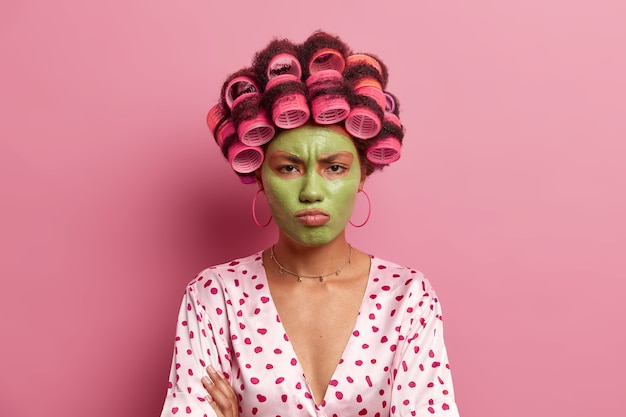 Beledigde ontevreden jonge vrouw past schoonheid groen gezichtsmasker toe, moe van het wachten op cosmetisch producteffect, draagt krulspelden op haar, vormt tegen rooskleurig. huisvrouw maakt kapsel.
