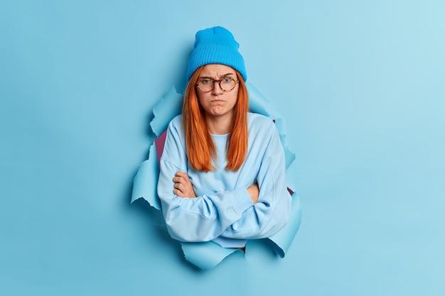 Beledigde, ontevreden vrouw voelt zich beledigd of verontwaardigd houdt armen over elkaar staat gehinderd in verdedigende houding heeft sombere uitdrukking draagt blauwe hoed en trui.