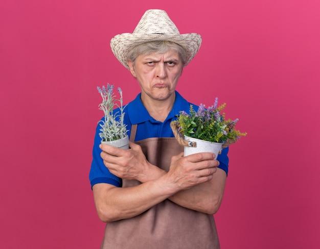 Beledigde oudere vrouwelijke tuinman die een tuinhoed draagt en bloempotten vasthoudt