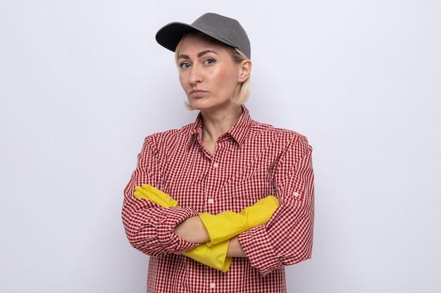 Beledigde schoonmaakster in geruit hemd en pet met rubberen handschoenen die naar de camera kijkt met gekruiste armen over een witte achtergrond