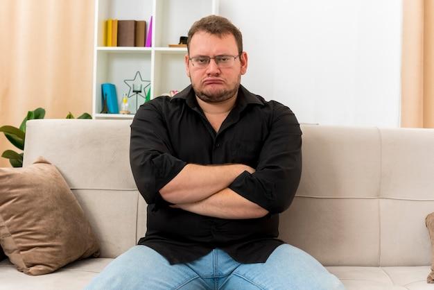 Beledigde volwassen slavische man in optische bril zit op fauteuil met gekruiste armen in de woonkamer