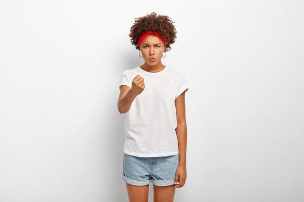 Beledigde woedende vrouw schudt vuist in waarschuwend gebaar, probeert iemand te bedreigen