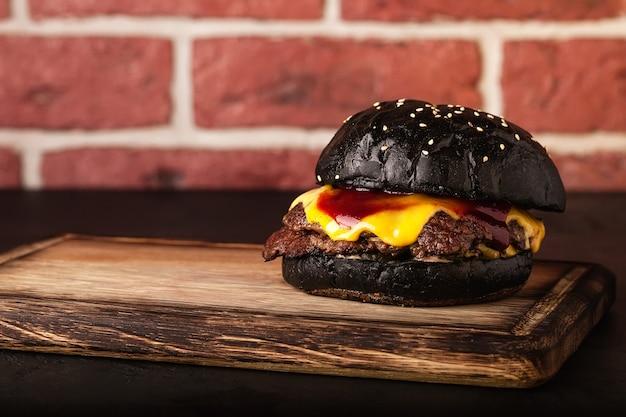 Belegd broodje. fast food. hamburger met vlees en groenten. zwarte burger.