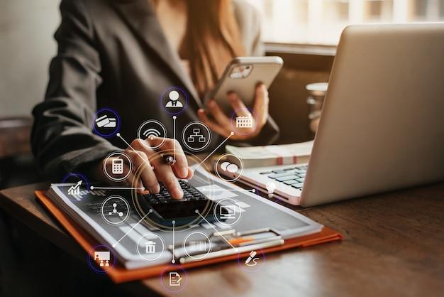 Beleggers berekenen de investeringskosten van de rekenmachine en houden een smartphone vast.