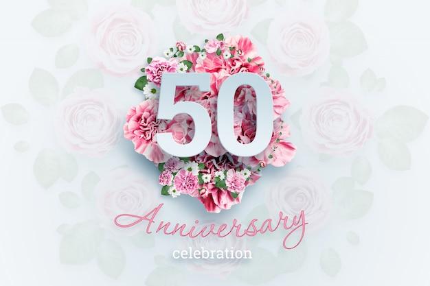 Belettering van 50 nummers en verjaardag viering tekst op roze bloemen.