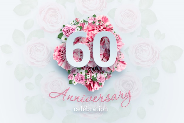 Belettering van 60 nummers en verjaardag viering tekst op roze bloemen.