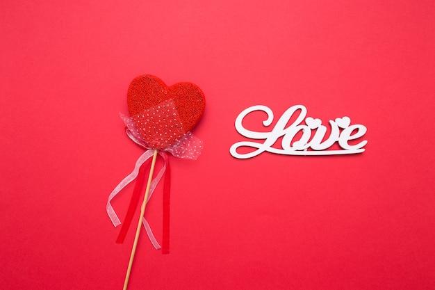 Belettering van houten letters liefde op een rode geïsoleerde achtergrond. hart in de vorm van snoep op een stokje.