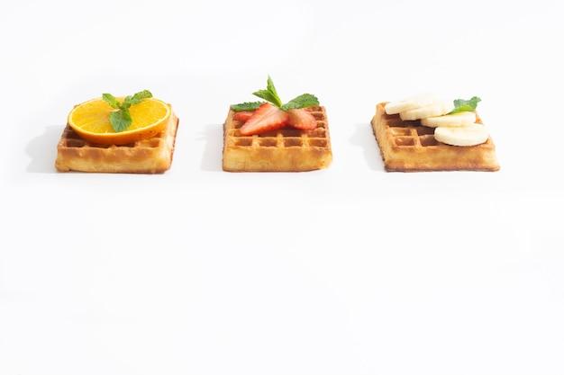 Belgische wafels met aardbei-banaan en sinaasappel met siroop op wit
