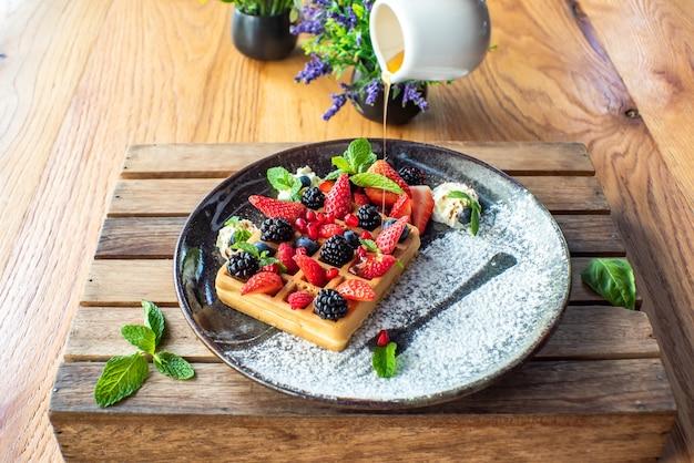 Belgische wafels met aardbeien, bosbessen, bramen en stroop