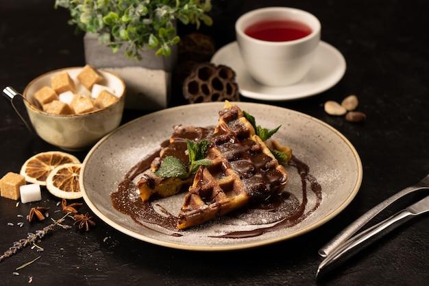 Belgische wafels met chocolade versierd met muntblaadjes. een mooi warm dessert voor thee of koffie.