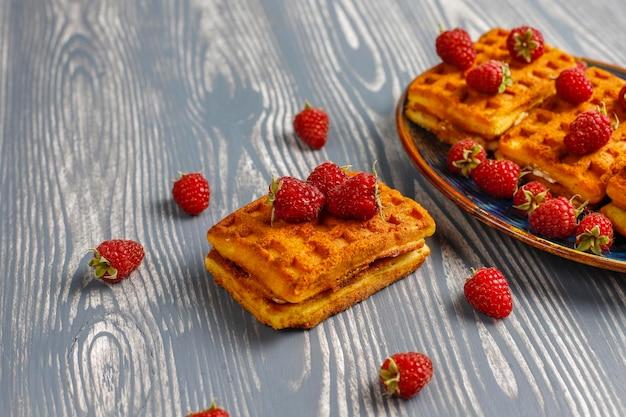 Belgische wafels met room en verse frambozen.