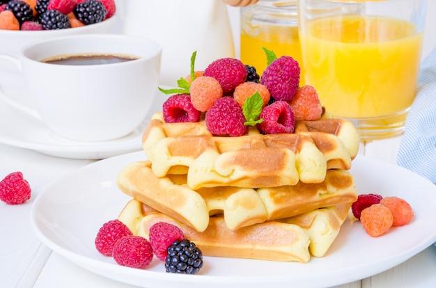 Belgische wafels met verse frambozen en bramen op een witte plaat voor het ontbijt.