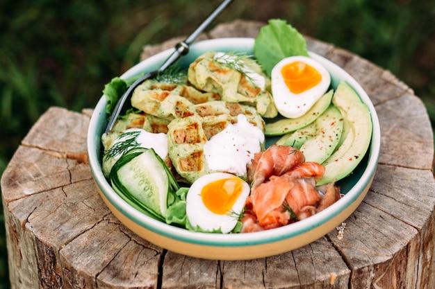 Belgische wafels met zalm, avocado en ei in een bord