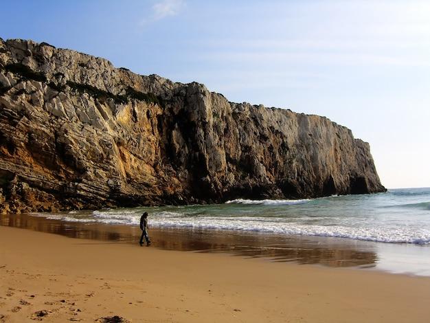 Beliche strand kust met rotsformaties aan de linkerkant en een jonge vrouw lopen op het zand.