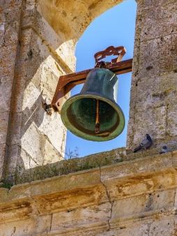 Bell in middeleeuwse stenen kerktoren met blauwe hemel.