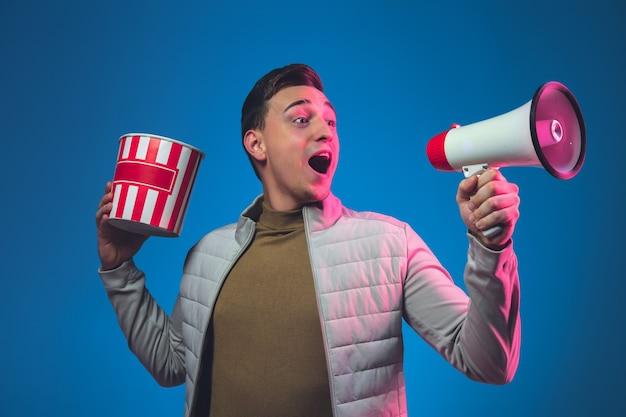 Bellen met speaker en popcorn. portret van een blanke man geïsoleerd op blauwe muur in roze neonlicht.