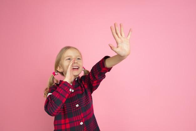 Bellen, schreeuwen. het portret van het kaukasische meisje op roze muur. mooi vrouwelijk model met blond haar.