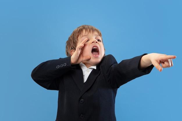 Bellen, schreeuwen. portret van een jonge orthodoxe joodse jongen geïsoleerd op blauwe muur. purim, zaken, festival, vakantie, jeugd, viering pesach of pesach, jodendom, religieconcept.