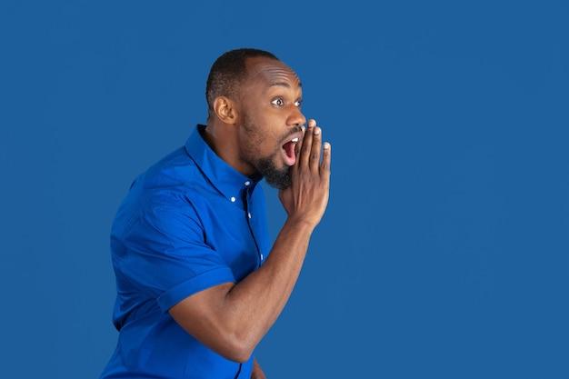 Bellen, schreeuwen. zwart-wit portret van jonge afro-amerikaanse man geïsoleerd op blauwe muur. mooi mannelijk model. menselijke emoties, gezichtsuitdrukking, verkoop, advertentieconcept. jeugd cultuur.