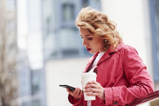 Bellen. volwassen mooie vrouw in warme rode jas wandelt in het weekend door de stad