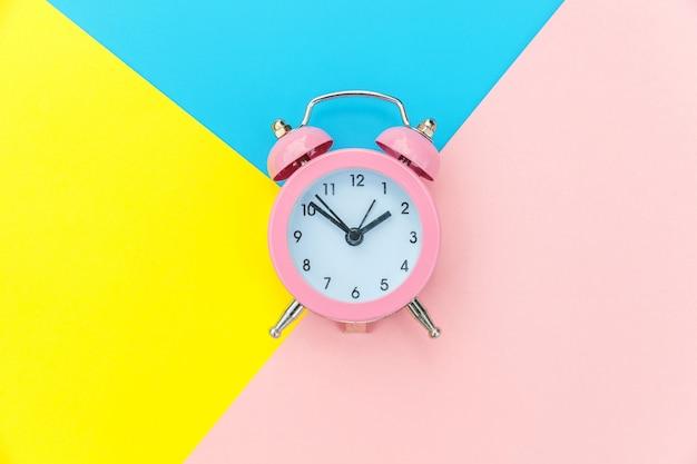 Bellende dubbele klok klassieke wekker die op blauwe gele roze pastelkleur kleurrijke geometrische achtergrond wordt geïsoleerd. rust uren tijd van leven goedemorgen nacht wakker wakker concept. plat lag bovenaanzicht kopie ruimte.
