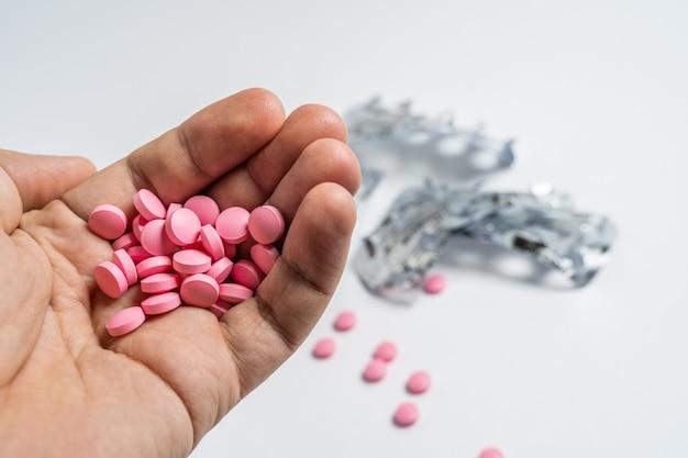 Bemant handen met pillen, morst pillen uit fles op witte achtergrond