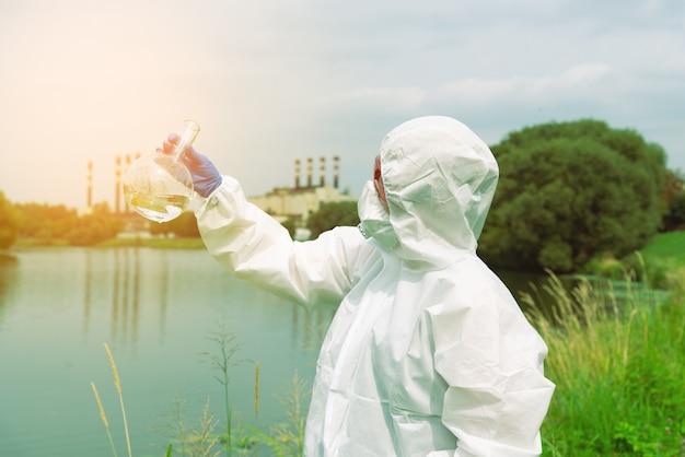 Bemonstering uit open water. een wetenschapper of bioloog neemt een watermonster in de buurt van een fabrieksinstallatie. een monster van water in een ronde chemische kolf.