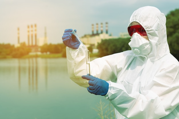 Bemonstering uit open water. een wetenschapper of bioloog neemt een watermonster in de buurt van een fabrieksinstallatie. watermonster in een chemische reageerbuis met een pipet.