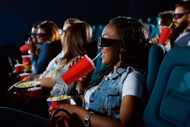 Ben benieuwd naar de nieuwe film. jonge afrikaanse vrouw die aan haar drankje nipt terwijl ze naar een film kijkt in de bioscoop met een 3d-bril