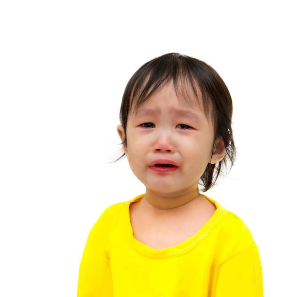 Ben droevige meisjezitting op witte vloer met het knippen van weg.