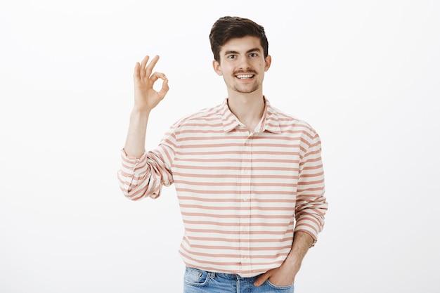 Ben het helemaal met je eens. binnen schot van kalme gelukkige blanke man met baard en snor, handen opsteken met oke gebaar, concept goedkeuren, denken idee is uitstekend, staande over grijze muur
