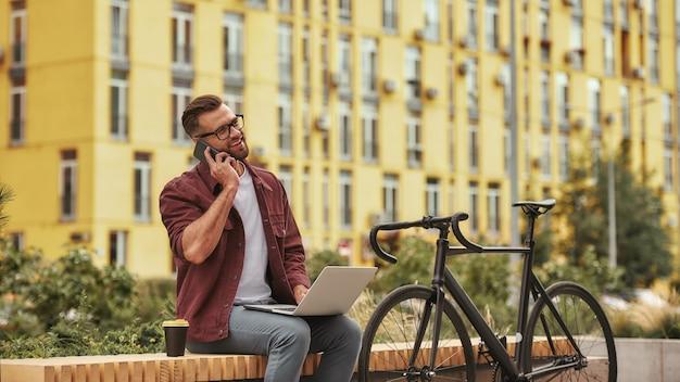 Ben het met je eens knappe en jonge man met stoppels in vrijetijdskleding die op laptop werkt