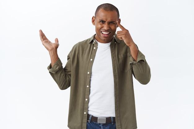 Ben je dom of zo. portret van ruzie met een geërgerde en gefrustreerde afro-amerikaanse man die naar links wijst naar een teleurstellende verknalde grafiek