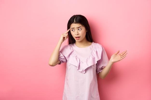 Ben je gek. geschokt aziatische vrouw wijzend op het hoofd en klagen, iemand gek of vreemd uitschelden, opzij kijken, staande tegen roze achtergrond.
