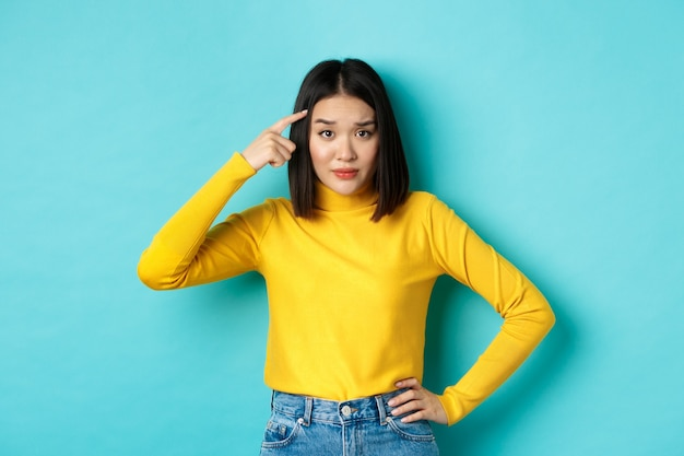 Ben je gek. portret van een sceptische aziatische vrouw die gek of stom iemand uitscheldt, vinger op het hoofd richt en met ontzetting, blauwe achtergrond naar camera staart.