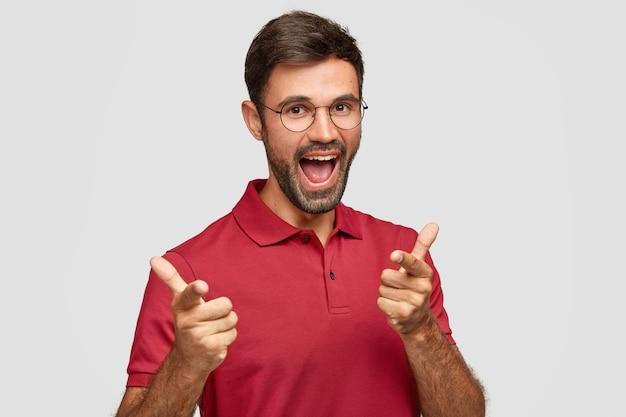Ben je klaar om te concurreren? gelukkig bebaarde jonge man ziet er positief uit, maakt keuze en wijst, selecteert iemand die vooraan staat, draagt casual licht t-shirt, geïsoleerd over witte muur